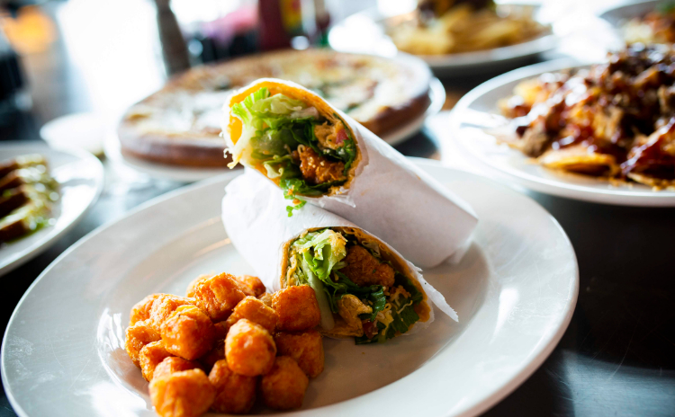 A wrap with a side of tater tots prepared by House Divded Restaurant & Sports Grill