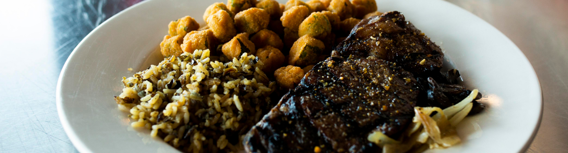 A plate of steak, rice and fried okra, prepared by House Divided